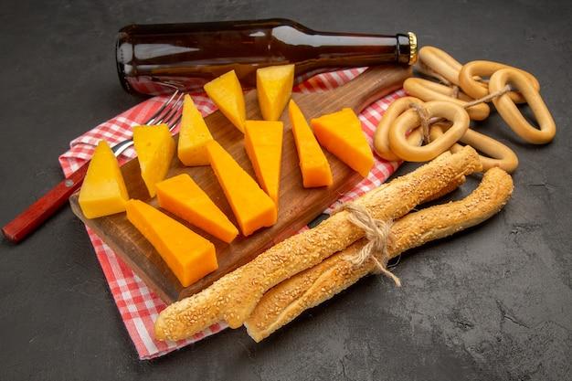Widok z przodu świeży pokrojony ser z bułeczkami i krakersami na ciemnoszarym posiłku zdjęcie śniadanie chipsy chrupiące jedzenie