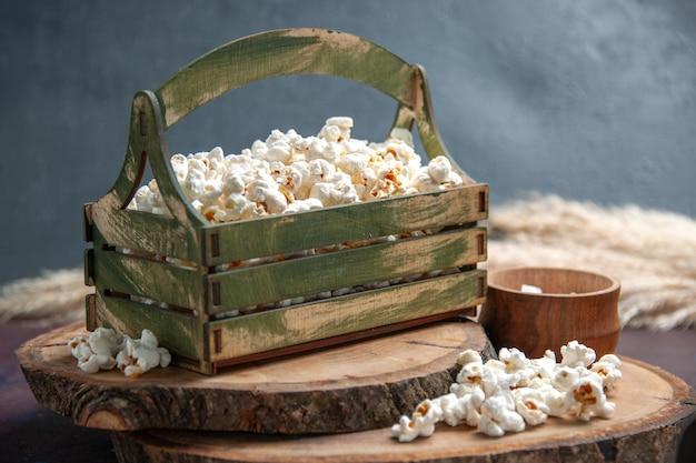Widok z przodu świeży popcorn na ciemnym biurku przekąski popcornowe jedzenie kukurydziane