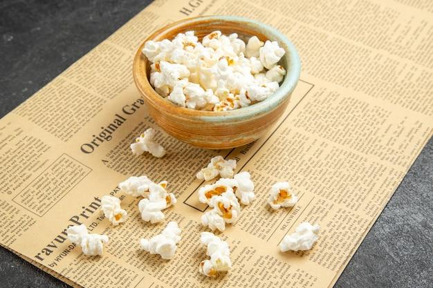 Widok z przodu świeży popcorn wewnątrz talerza na ciemnym tle przekąska film kino jedzenie kukurydza