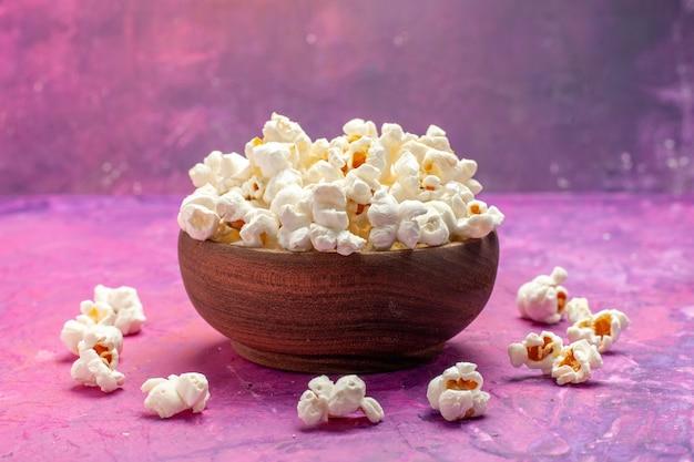 Widok z przodu świeży popcorn wewnątrz talerza na różowym stole kinowym w kolorze filmu