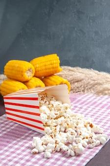 Widok z przodu świeży popcorn z żółtymi odciskami na ciemnej podłodze przekąska popcorn kukurydza