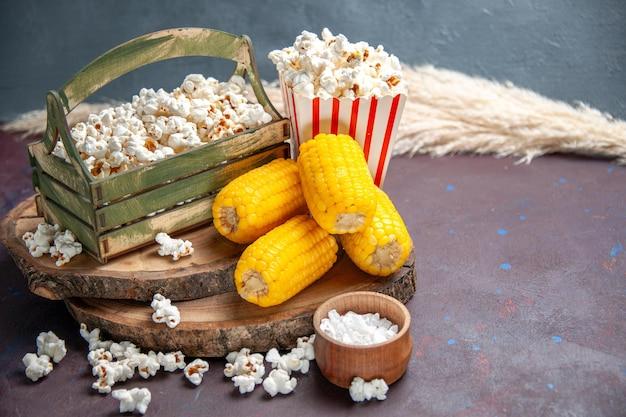 Widok z przodu świeży popcorn z żółtymi odciskami na ciemnej powierzchni przekąska popcorn spożywczy kukurydza