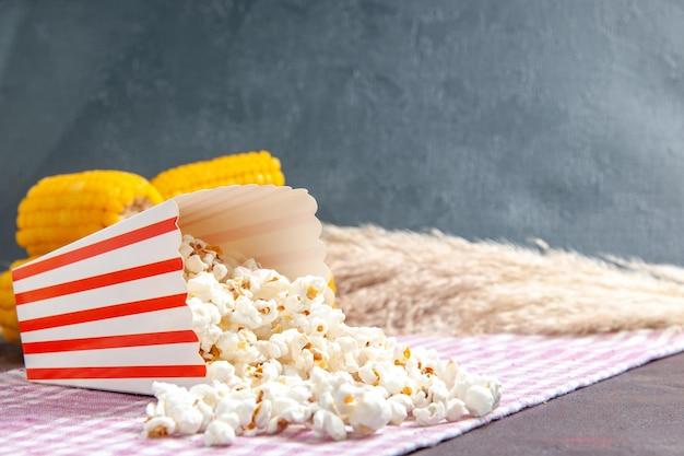 Widok z przodu świeży popcorn z żółtymi odciskami na ciemnej powierzchni przekąska popcornowa kukurydza