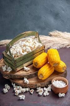 Widok z przodu świeży popcorn z żółtymi odciskami na ciemnej powierzchni przekąski popcornowe jedzenie kukurydziane