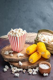 Widok z przodu świeży popcorn z żółtymi odciskami na ciemnym biurku przekąska popcornowa kukurydza