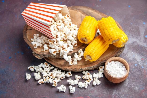 Widok z przodu świeży popcorn z żółtymi pokrojonymi odciskami na ciemnej podłodze przekąska popcorn spożywczy kukurydza
