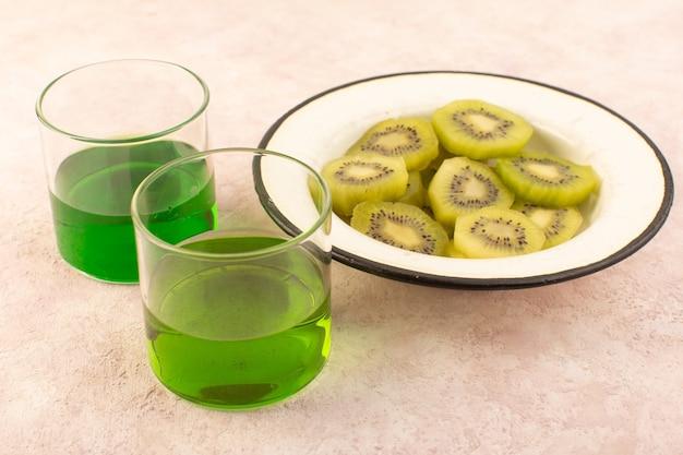 Widok z przodu świeży sok z kiwi w kolorze zielonym ze świeżymi plasterkami kiwi na różowym biurku owoce egzotyczne tropikalne