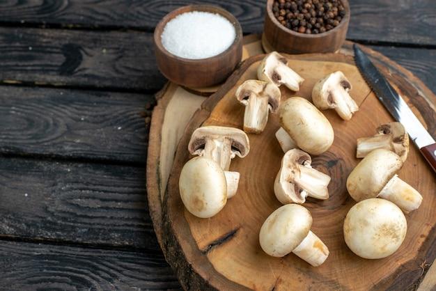Widok z przodu świeżych grzybów i noża na drewnianym ręczniku i przyprawach na czarnym tle