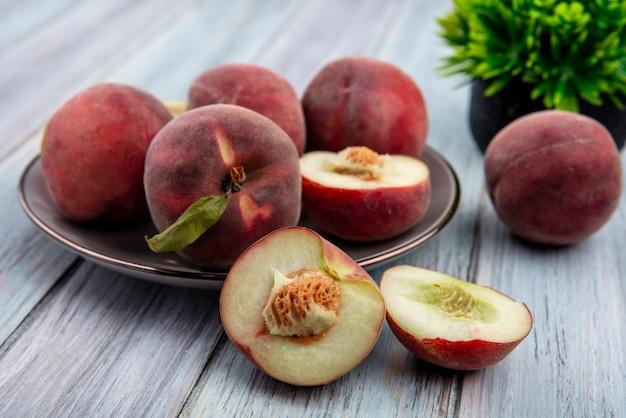 Widok z przodu świeżych słodkich pysznych brzoskwiń pół na talerzu na szarej powierzchni drewnianej
