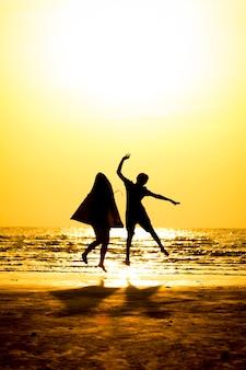 Widok z przodu sylwetka młodego człowieka i młoda dziewczyna skacząc nad morzem na tle zachodu słońca.