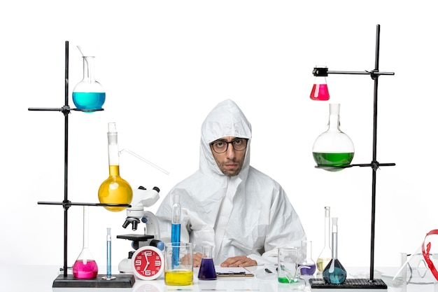 Widok z przodu szalony naukowiec mężczyzna w specjalnym kombinezonie ochronnym, siedzący wokół stołu z roztworami na białym tle choroba covid laboratory science virus