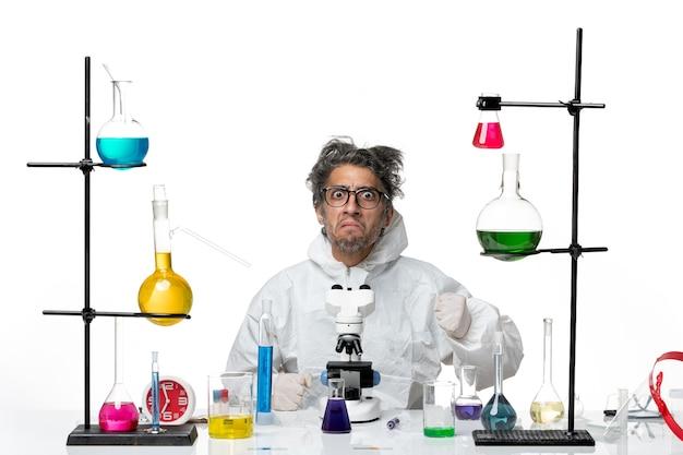 Widok z przodu szalony naukowiec mężczyzna w specjalnym kombinezonie ochronnym, siedzący wokół stołu z roztworami na białym tle choroba laboratoryjna wirus naukowy