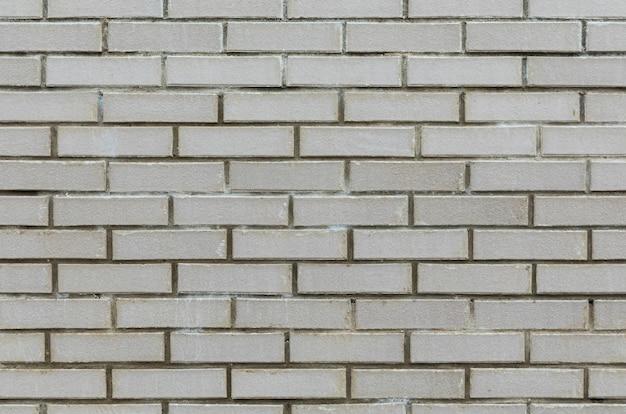 Widok z przodu szarej cementowej ściany wyłożone płytkami z cegły.