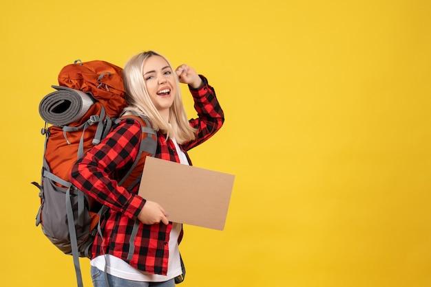 Widok z przodu szczęśliwa blondynka z plecakiem trzyma karton