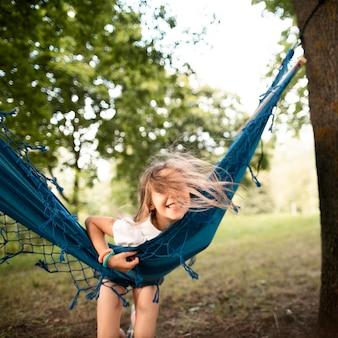 Widok z przodu szczęśliwa dziewczyna w hamaku