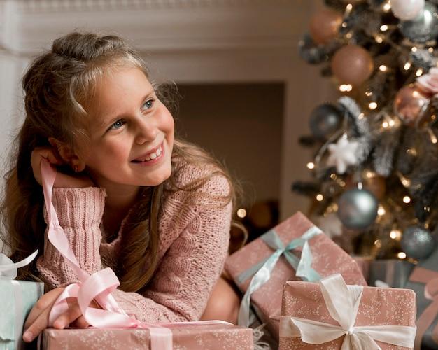 Widok z przodu szczęśliwa dziewczyna z prezentami i choinką