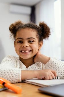 Widok z przodu szczęśliwa dziewczynka w domu podczas szkoły online z laptopem