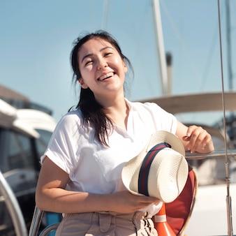 Widok z przodu szczęśliwa kobieta pozuje z kapeluszem