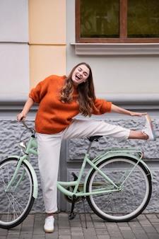 Widok z przodu szczęśliwa kobieta pozuje z rowerem na zewnątrz