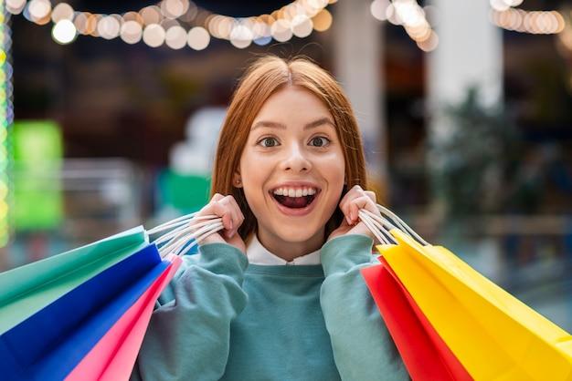 Widok z przodu szczęśliwa kobieta trzyma kolorowe torby