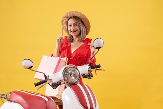 Widok z przodu szczęśliwa kobieta w czerwonej sukience na motorowerze trzymając torby na zakupy i kartę wskazującą na sufit