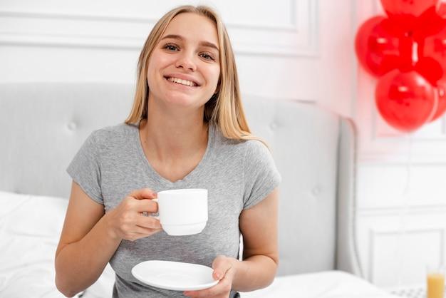 Widok z przodu szczęśliwa kobieta z kawą w sypialni