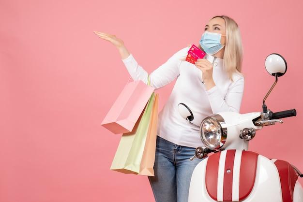 Widok z przodu szczęśliwa młoda dama z maską trzymając torby na zakupy i karty w pobliżu motoroweru