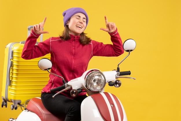 Widok z przodu szczęśliwa młoda dziewczyna na motorowerze ze specjalnym gestem ręki