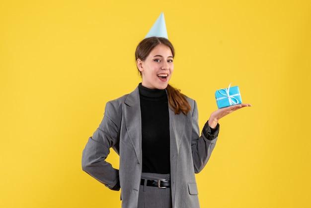 Widok z przodu szczęśliwa młoda dziewczyna trzyma jej prezent z czapką