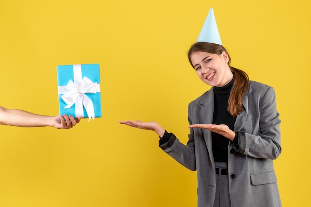 Widok z przodu szczęśliwa młoda dziewczyna z czapką otrzymującą prezenty świąteczne