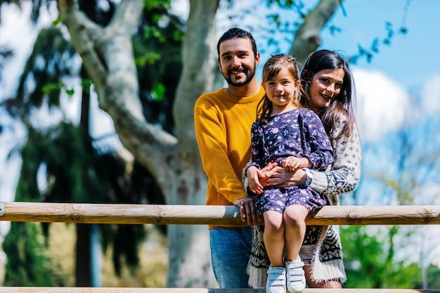 Widok z przodu szczęśliwą rodzinę w parku. ojciec matka i syn razem w przyrodzie
