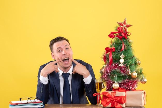 Widok z przodu szczęśliwego człowieka siedzącego przy stole w pobliżu choinki i prezentów na żółto