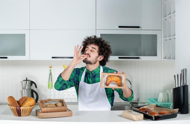 Widok z przodu szczęśliwego mężczyzny trzymającego świeżo upieczone ciasto w małym pudełku i wykonującego doskonały gest w białej kuchni