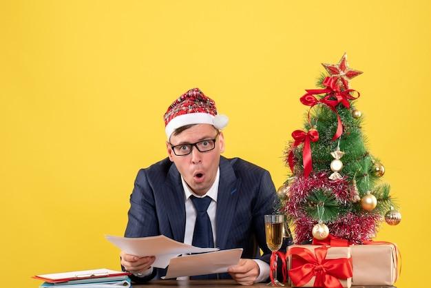 Widok z przodu szczęśliwy człowiek biznesu sprawdzanie dokumentów siedzi przy stole w pobliżu choinki i przedstawia na żółto
