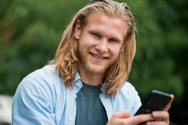 Widok z przodu szczęśliwy człowiek na zewnątrz z telefonem