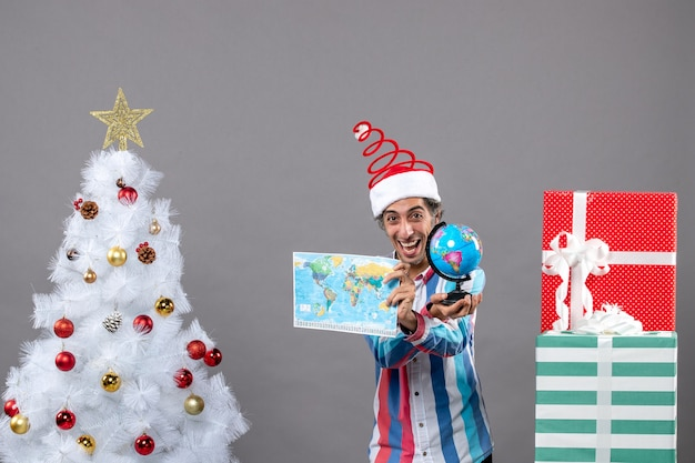 Widok z przodu szczęśliwy człowiek pokazujący mapę świata i kulę ziemską
