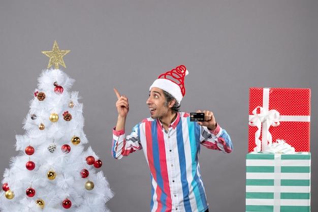 Widok z przodu szczęśliwy człowiek z kartą kredytową przedstawiającą gwiazdę świąteczną stojącą w pobliżu różnych prezentów