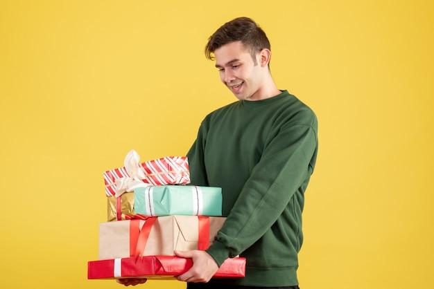 Widok z przodu szczęśliwy człowiek z zielonym swetrem, trzymając prezenty na żółto
