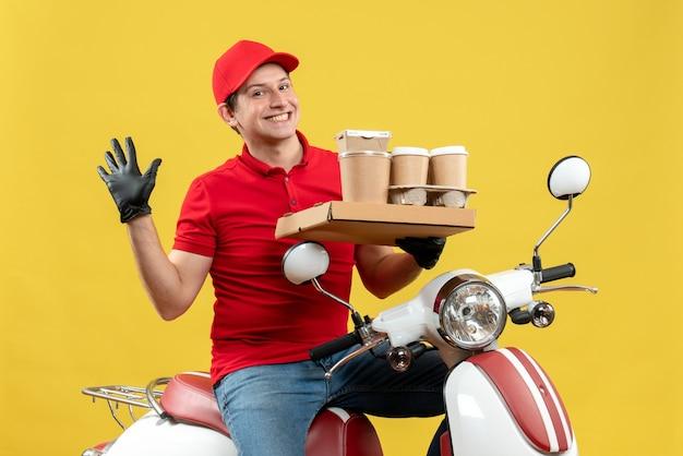 Widok z przodu szczęśliwy kurier ubrany w czerwoną bluzkę i kapeluszowe rękawiczki w masce medycznej dostarczania zamówienia siedzącego na skuterze przechowującym zamówienia
