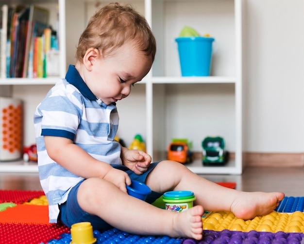 Widok z przodu szczęśliwy ładny chłopczyk bawi się zabawkami