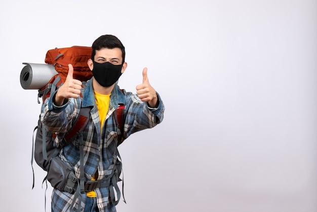 Widok z przodu szczęśliwy męski podróżnik z plecakiem i maską, dając kciuki do góry