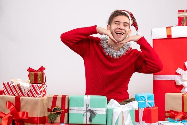 Widok z przodu szczęśliwy młody chłopak z maską siedzi wokół świątecznych prezentów