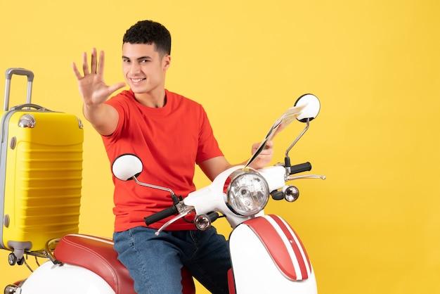 Widok z przodu szczęśliwy młody człowiek na mapie gospodarstwa motoroweru