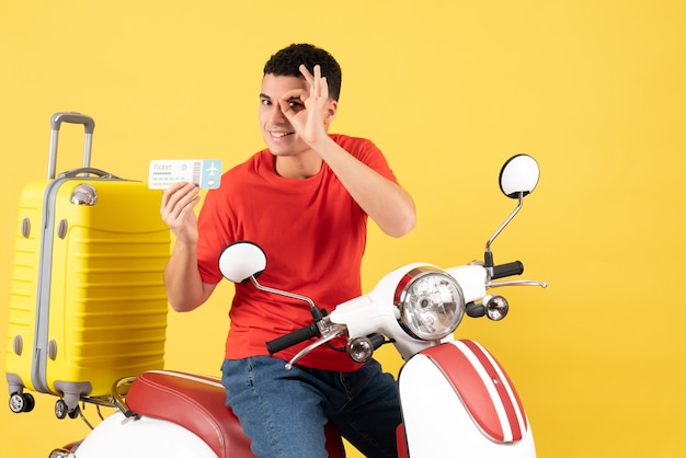 Widok z przodu szczęśliwy młody człowiek na motorowerze posiadający bilet stawiając znak okey przed jego znakiem