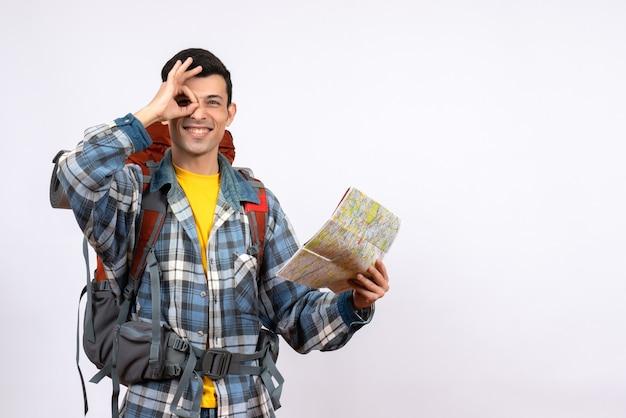 Widok z przodu szczęśliwy młody obozowicz z plecakiem trzymając mapę, robiąc znak ok