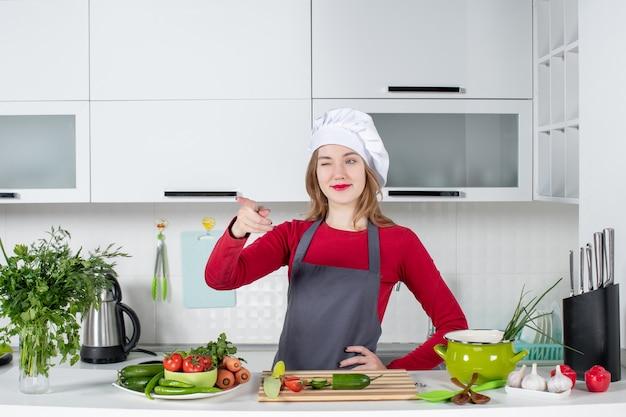 Widok z przodu szefa kuchni w kapeluszu kucharza, wskazując palcem wskazującym z przodu