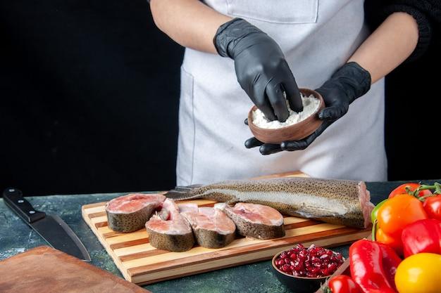 Widok z przodu szefa kuchni z fartuchem posypującym mąkę na plastry surowej ryby na stole kuchennym