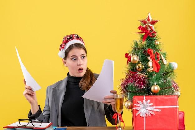 Widok z przodu szeroko-eyed dziewczyna z kapeluszem xmas siedzi przy stole patrząc na dokumenty xmas tree i prezenty koktajl