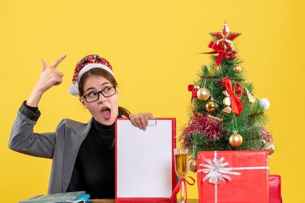 Widok z przodu szeroko-eyed dziewczyna z kapeluszem xmas siedzi przy stole, podnosząc rękę choinki i prezenty koktajlowe