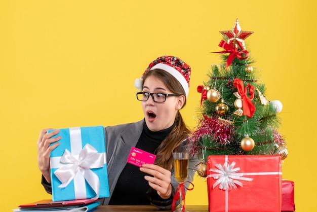 Widok z przodu szeroko-eyed dziewczyna z kapeluszem xmas siedzi przy stole trzymając kartę drzewo xmas i prezenty koktajl